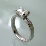 Elegantly styled emerald cut diamond ring, set East-West
