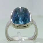 Bezel set platinum ring with blue rutilated aquamarine