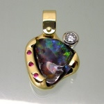 Gold pendant with a black opal bursting with red, blue and green
